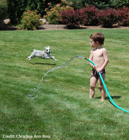 A child pouring water from a hose onto the ground.