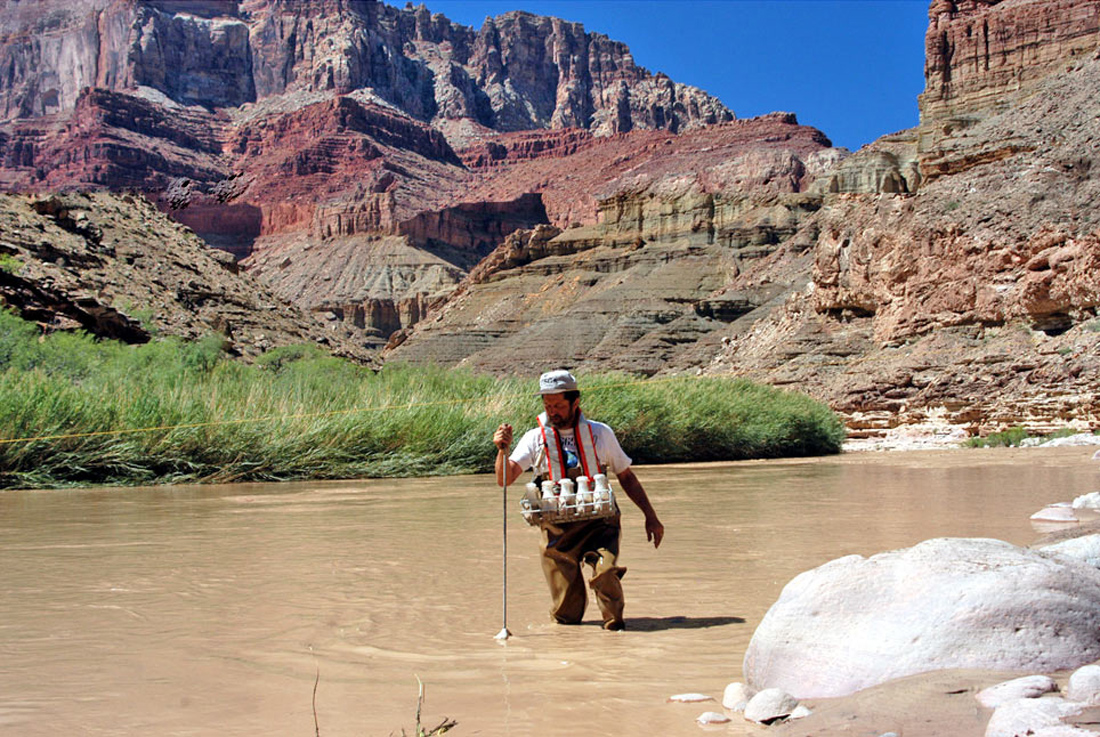 A USGS hydrographer collecting a suspended-sediment water sample from the Little Colorado River, a kilometer upstream from the Colorado River, Grand Canyon, Arizona, USA