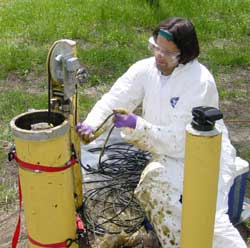 [Photo of scientist pulling radar cable, with oil splased onto protective clothing]