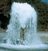[Photo: Ground water flowing out of well.]